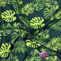 waterproof fabric green leaves of monstera on a dark green background
